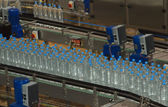 Plastic water bottles on conveyor and water bottling machine ind — Stock Photo