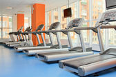 Gym with windows and running machines in fitness center — Stock Photo