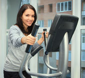 Young woman doing exercise on a elliptical trainer — Stok fotoğraf