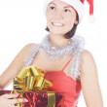 Beautiful christmas woman in santa hat holding gift — Stock Photo #4247484