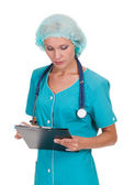 Female doctor holding a clipboard and reading — Stock Photo