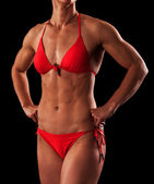 Muscular female body against black background. — Stock Photo