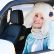 Happy woman in white fur hat in a car — Stock Photo #20726045