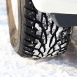 Car wheel on a white snow - Stock Photo