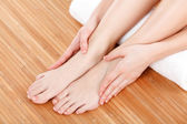 Beautiful female hands and feet with white towel — Stock Photo
