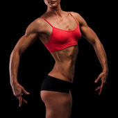 Muscular strong woman on a black background — Stock Photo