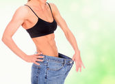 Woman with strong abs shows her old big jeans — Stock Photo
