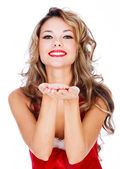 Cute young female in red dress blowing a kiss at you — Stock Photo