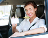 Girl in a car showing an empty white card for your message — Stock Photo