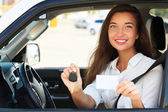 Girl in a car showing a key and an empty white card — Stock Photo