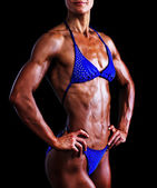 Slim muscled woman against black background — Stock Photo