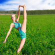 Stock Photo: Womdoing splits in green field