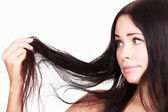 Brunette woman is not happy with her fragile hair — Stock Photo