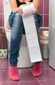 Woman in a toilet with a big hank of sanitary paper — Stock Photo