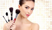 Pretty woman with cosmetic brushes — Stockfoto