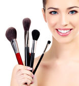 Female with cosmetic brushes, white background, copyspace — Stock Photo