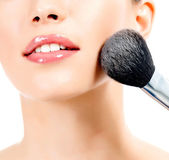 Pretty woman with a cosmetic brush, white background — Stock Photo
