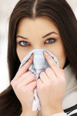 Woman with a cold holding a tissue, outdoors — Stockfoto