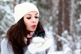 Beautiful young woman in knitted hat and sweater blows on hot te — Stock Photo