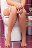Smoking woman in a toilet — Foto Stock