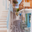 Narrow street of Greek island with stairs, flowers and street cafe. — Stockfoto #26974499