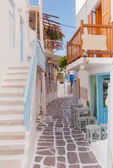 Narrow street of Greek island with stairs, flowers and street cafe. — Stock Photo