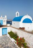 与海在岛上的背景上的蓝色圆顶的古典希腊教会。... — 图库照片