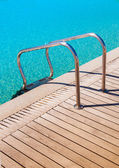 Metal railings in the pool near the wooden flooring — Stock Photo