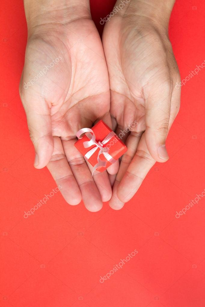 Red gift box with ribbon in hand isolated in red background — Stock Photo #12706084