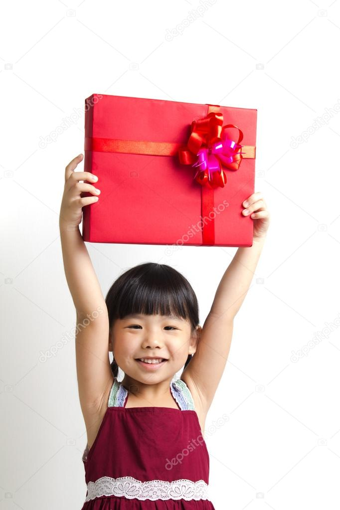 Asian child girl hold up high a red gift box — Stock Photo #14390431