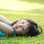 Child lying on grass — Stock Photo #18788383
