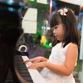 Little Asian girl playing piano — Stock Photo