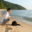 Royalty-Free Stock Photo: Man with dog at beach