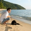 Man with dog at beach — Stock Photo