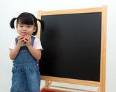 Female preschooler with apple in hand — Stock Photo