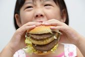 Kid eating big burger — Stock Photo