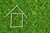 Model house on green grass — Stock Photo