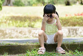 Little kid sitting in the park — Stock Photo