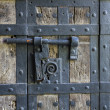 Ancient iron lock with latch on aged boarded door. — Stock Photo #32674977