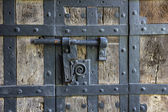 Ancient iron lock with latch on aged boarded door. — Stock Photo