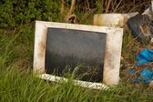 Discarded old TV set on a field — Stock Photo
