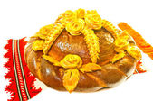 Bread decorated with flowers and wheat ears. Isolated on white b — Stock Photo