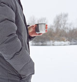Cup with hot tea in a hike when it is snowing — Stock Photo