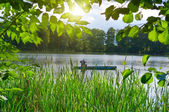 Inveterate fisherman in a boat on the lake. Summer fishing — Stock Photo