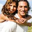 Young man giving piggyback ride to woman — Stock Photo #1370262