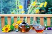 Herbal tea in teapot and cup. — Stock Photo
