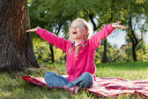 Happy little girl with hands up in summer park — Stock Photo