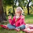 Little girl relaxing in yoga pose on grass in a park — Stock Photo #12597916