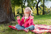 Little girl relaxing in yoga pose on grass in a park — Stockfoto