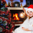 Girl in a Santa hat decorating Christmas tree, fireplace on back — Stock Photo